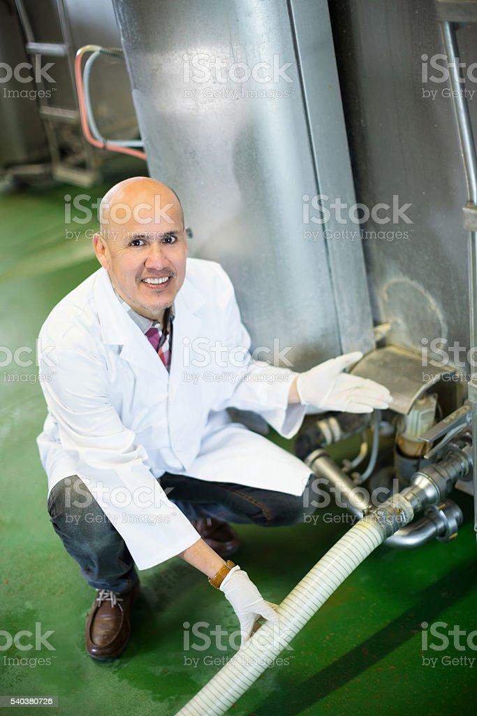 Portrait of farmer near cisterns with milk stock photo