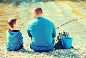 Portrait of father and son fishing with rods