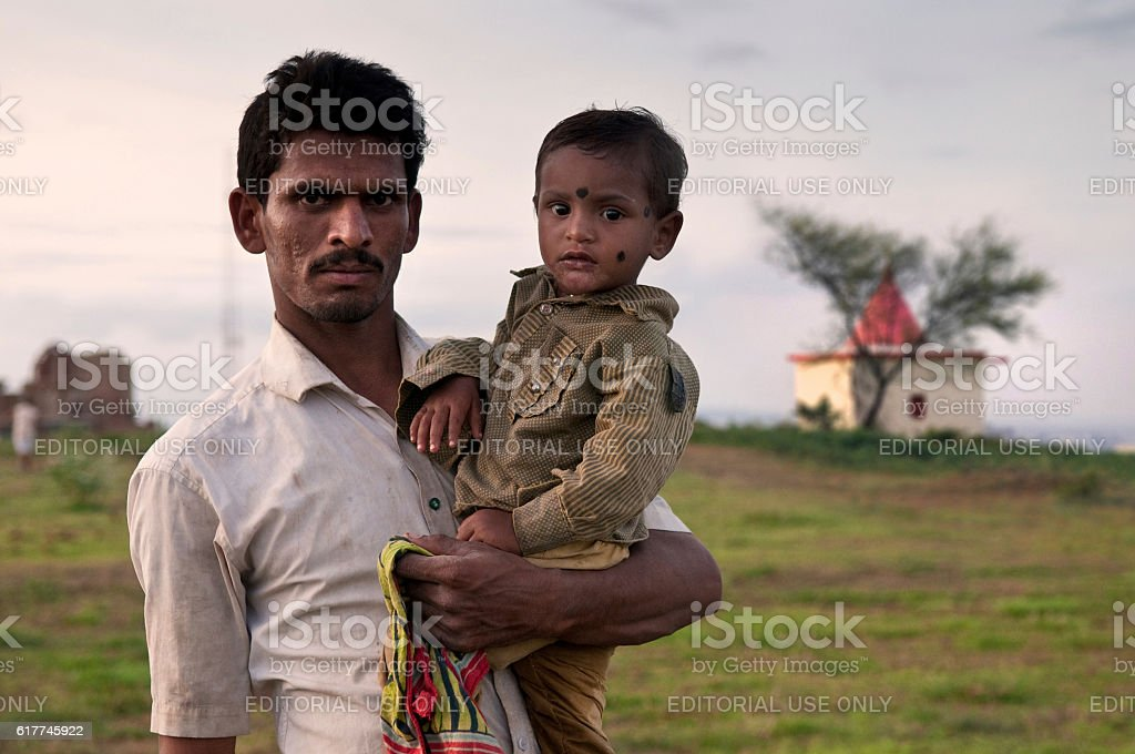 Portrait of father and son in rural India. stock photo