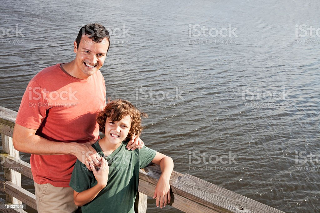 Portrait of father and son outdoors by water stock photo