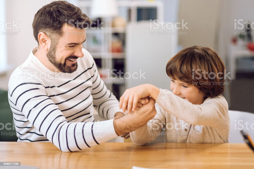 portrait of father and son playing at home stock photo