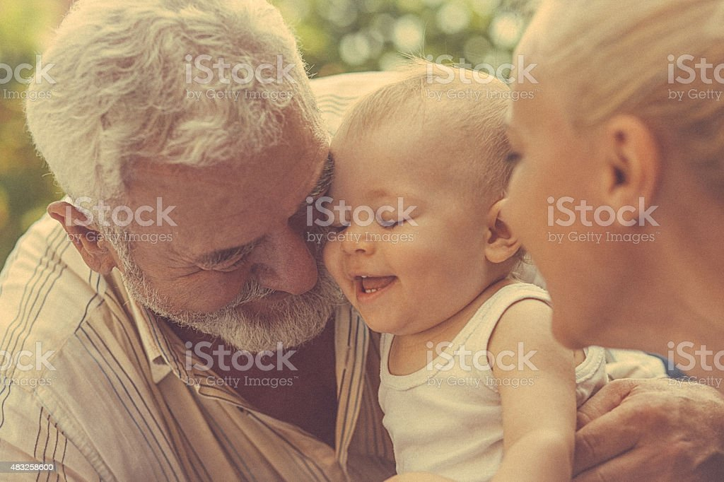 Portrait of father, daughter and grandchild in the park stock photo