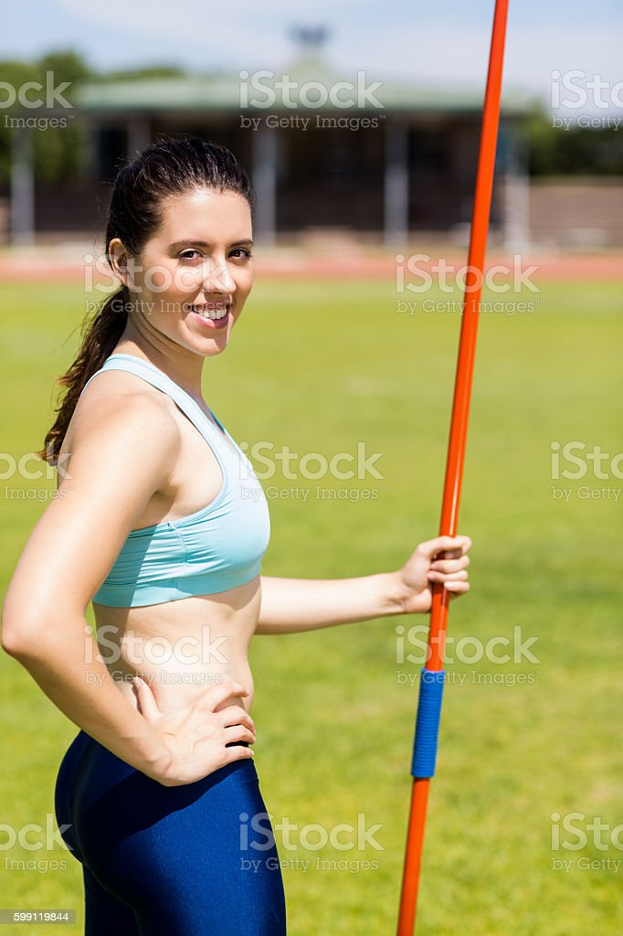 Portrait of female athlete standing with javelin stock photo