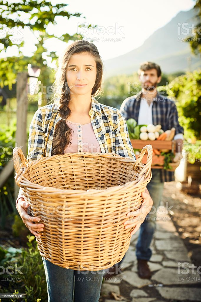 Portrait of female carrying wicker basket at organic farm stock photo