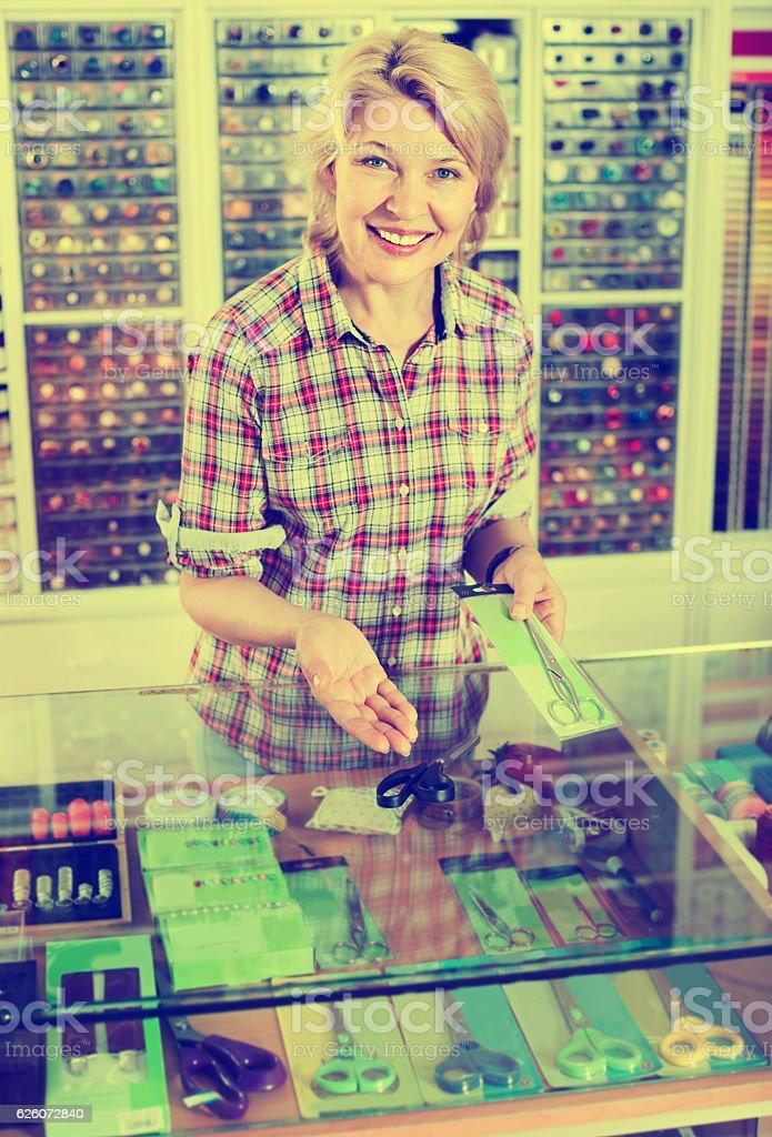 Portrait of female cashier standing at cash desk with scissors stock photo