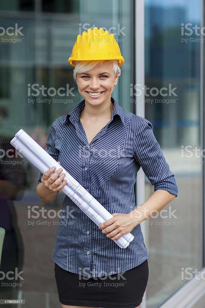 Portrait of female constructor with blueprints royalty-free stock photo