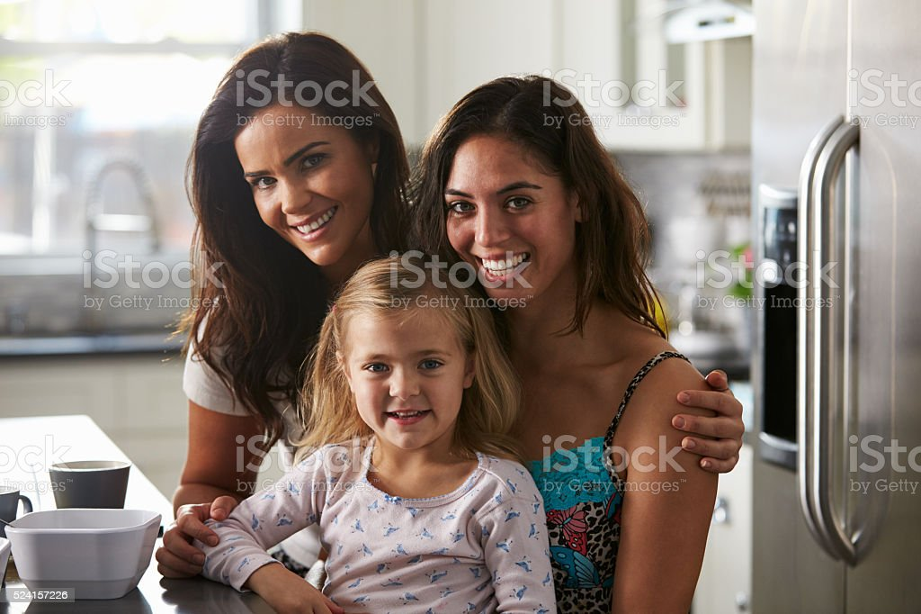 Portrait of female couple in the kitchen with their daughter stock photo