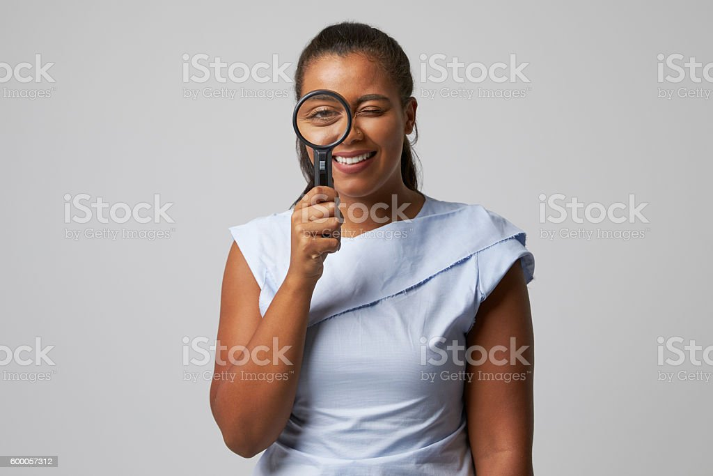 Portrait Of Female Criminologist With Magnifying Glass stock photo