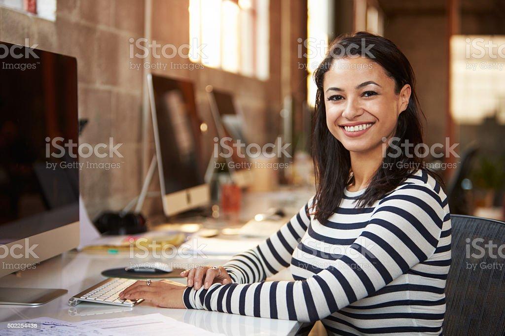 Portrait Of Female Designer Working At Desk In Modern Office stock photo