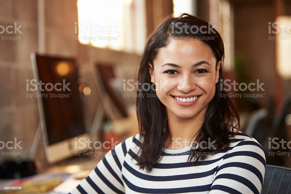 Portrait Of Female Designer Working At Desk In Modern Office stock photo