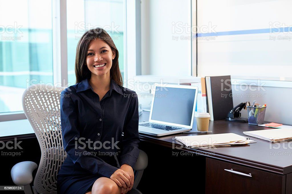 Portrait Of Female Doctor Sitting At Desk In Office stock photo