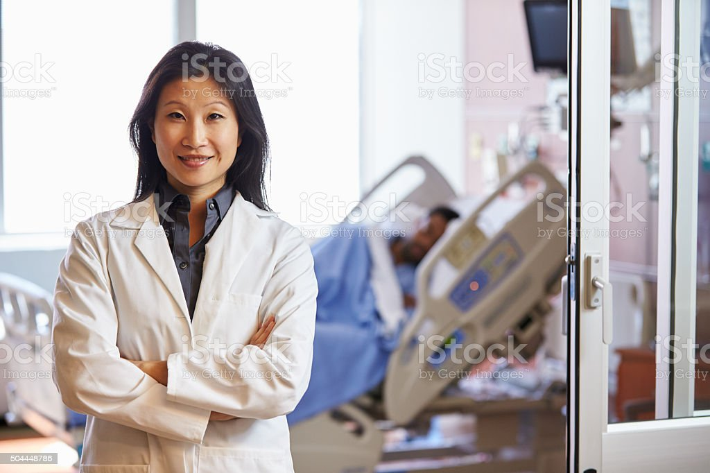 Portrait Of Female Doctor With Patient In Background stock photo