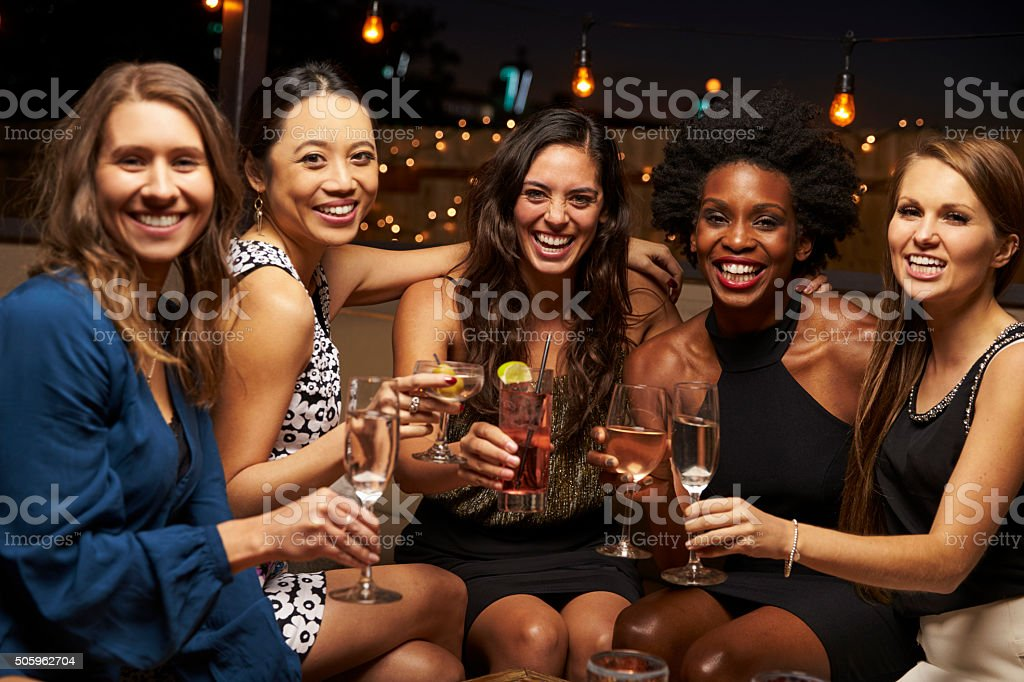 Portrait Of Female Friends Enjoying Night Out At Rooftop Bar stock photo