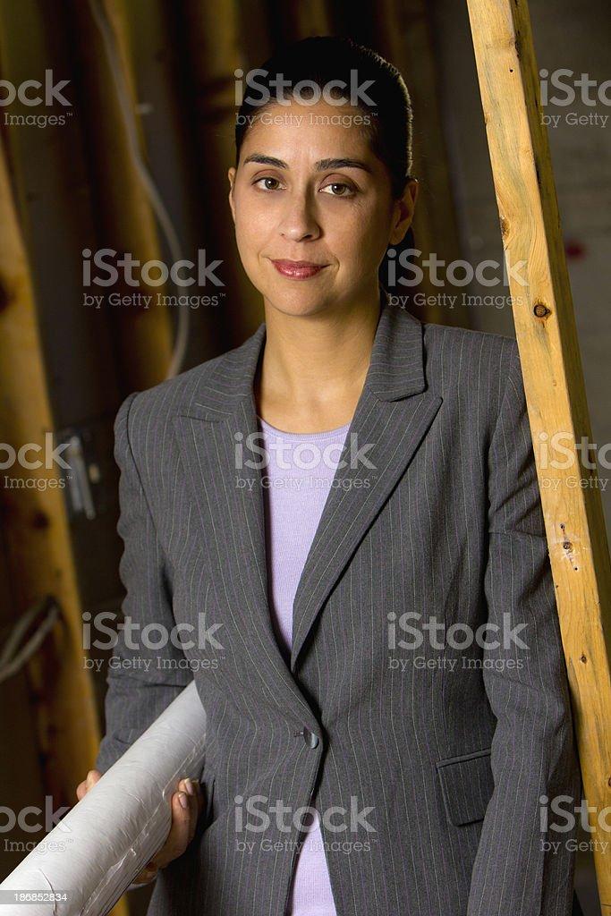 Portrait of female hispanic architect with blueprints royalty-free stock photo