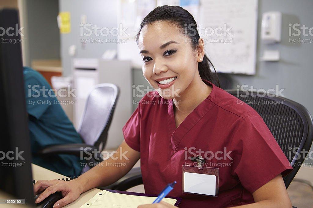 Portrait Of Female Nurse Working At Nurses Station stock photo