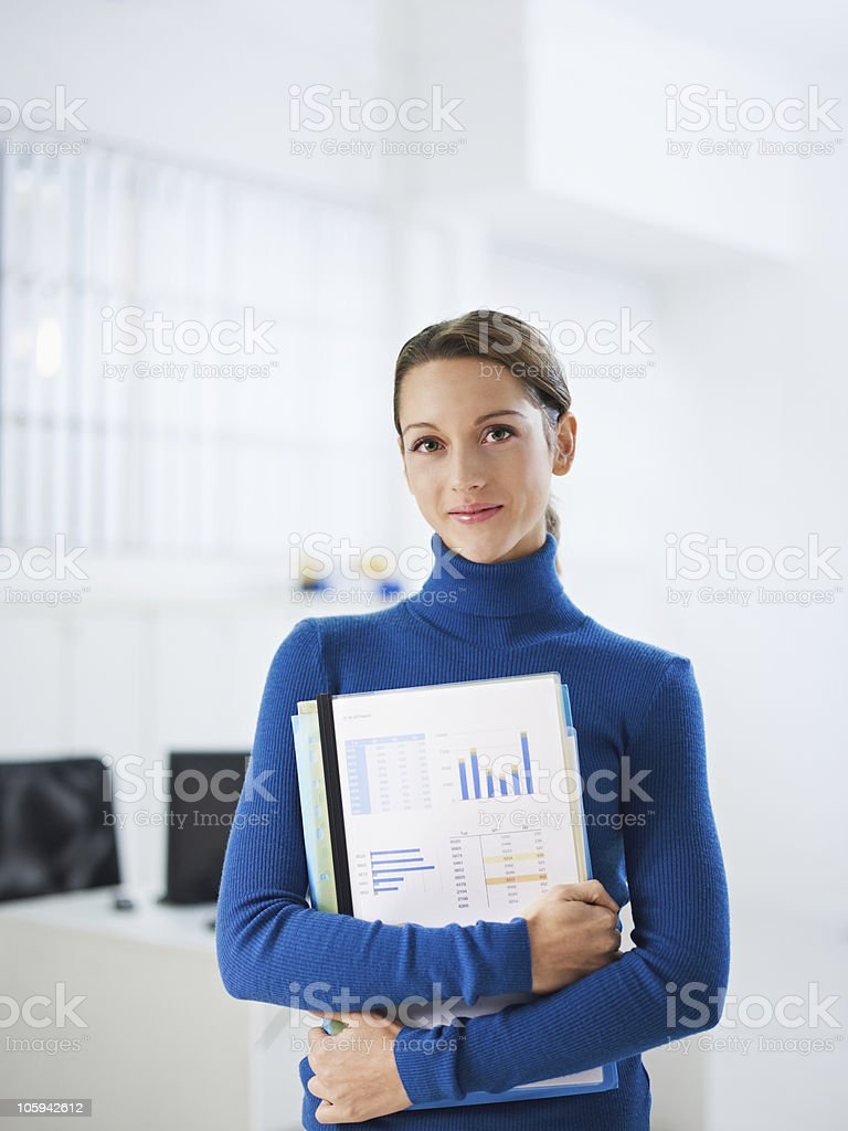 Portrait of female office assistance holding work products stock photo
