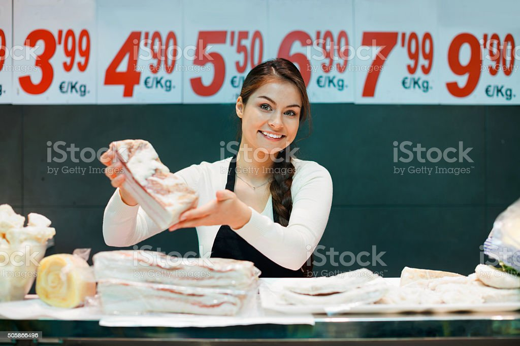 Portrait of female seller offering salo and lard stock photo