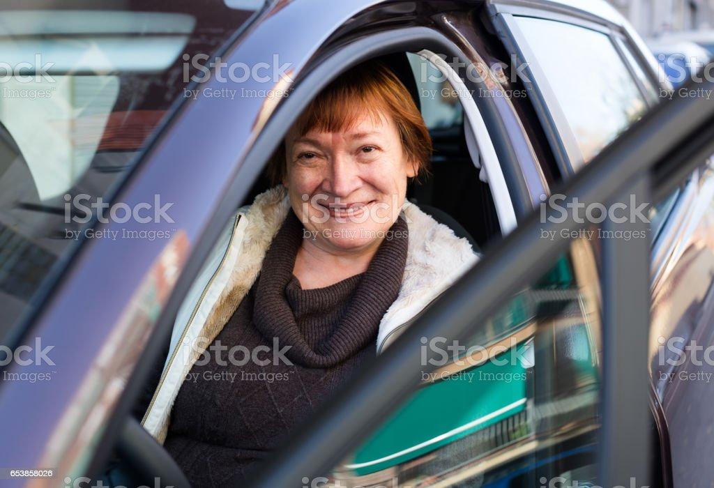 Portrait of female senior driver in car stock photo