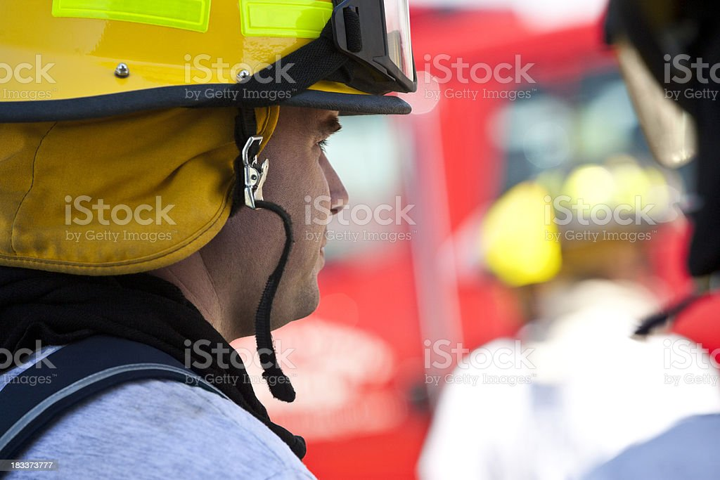 Portrait of Firefighter Looking at Action With Firetruck in Background royalty-free stock photo