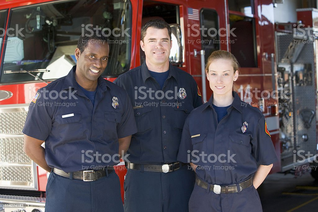 Portrait of firefighters standing by a fire engine royalty-free stock photo