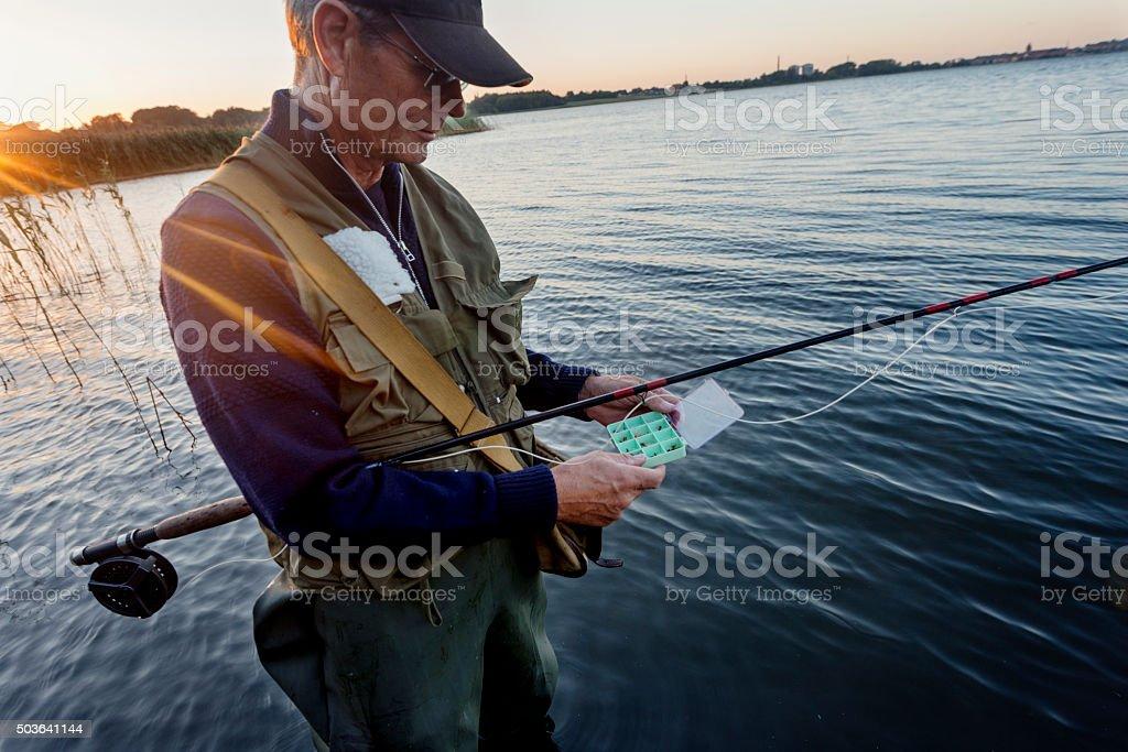 Portrait of Fisherman Tying a Fly on Stege Nor Denmark stock photo
