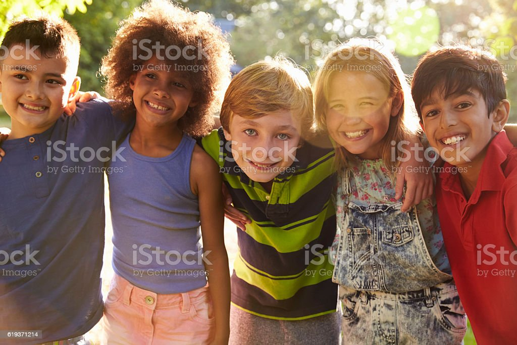Portrait Of Five Children Having Fun Outdoors Together stock photo