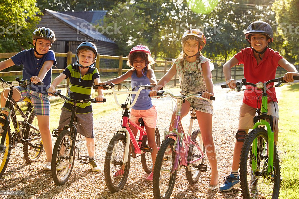 Portrait Of Five Children On Cycle Ride Together stock photo