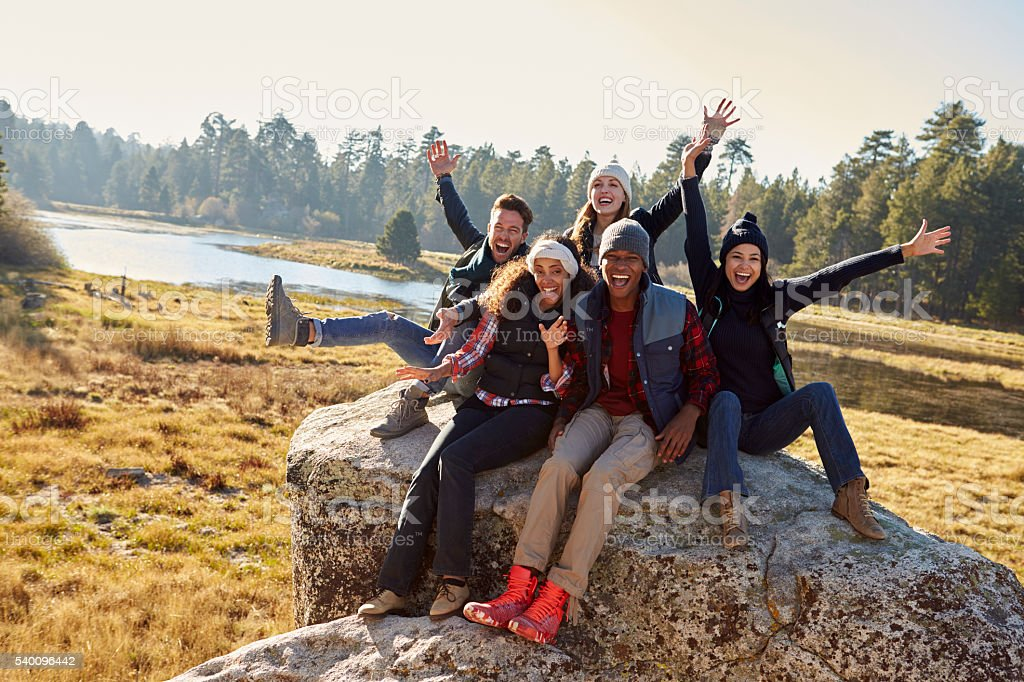 Portrait of five friends sitting on a rock in countryside stock photo