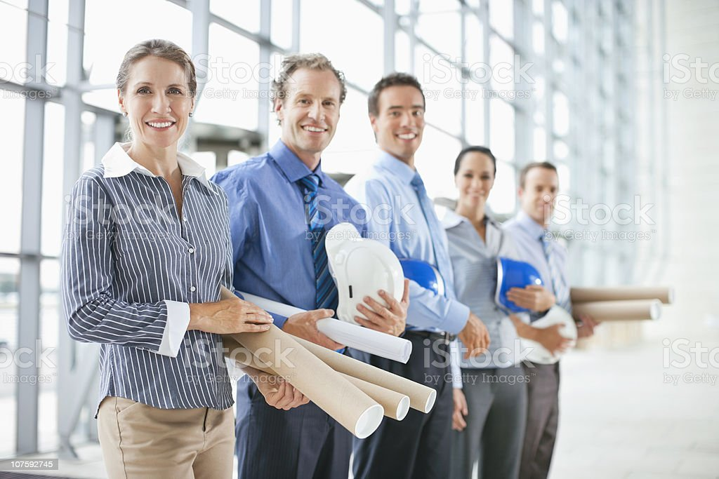Portrait of five male and female architects with hardhats and blueprints in office royalty-free stock photo