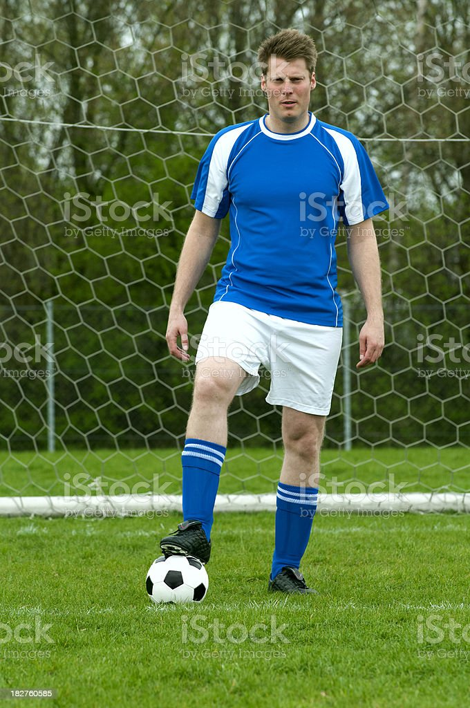 Portrait of football player standing on field with soccer ball royalty-free stock photo