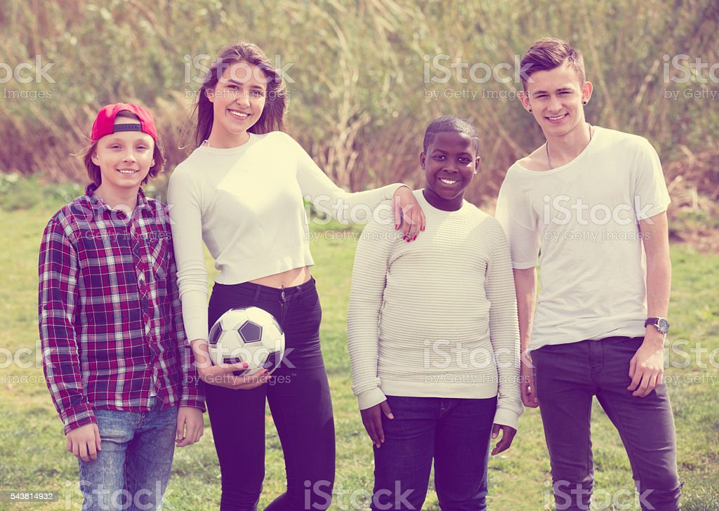 Portrait of four friends posing on countryside field with ball stock photo