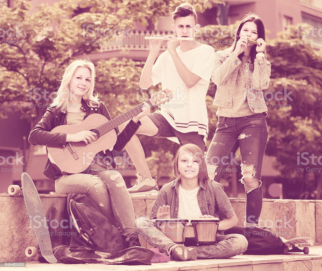 Portrait of four teenagers playing music together outdoors stock photo