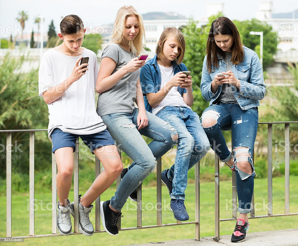 Portrait of four teenagers sitting with their mobile phones outd stock photo