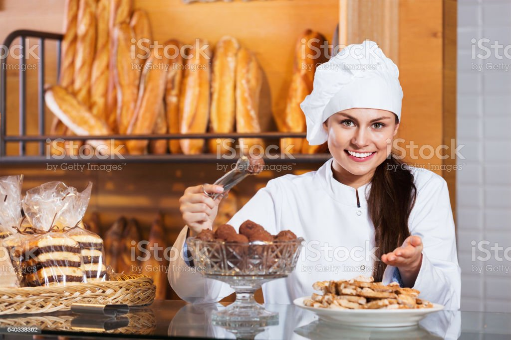 Portrait of friendly  young woman at bakery display stock photo