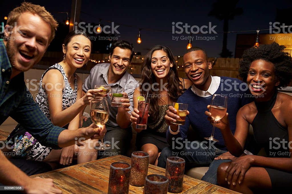 Portrait Of Friends Enjoying Night Out At Rooftop Bar stock photo