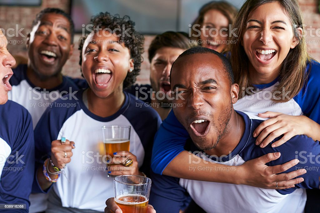 Portrait Of Friends Watching Game In Sports Bar On Screens stock photo