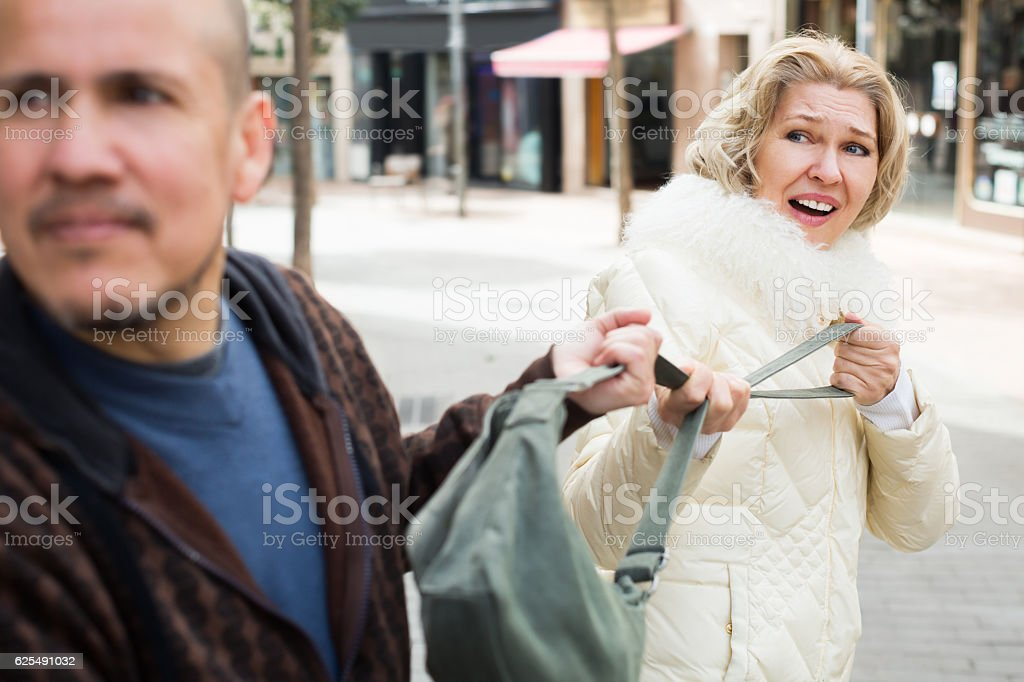 Portrait of frightened woman and robber stock photo
