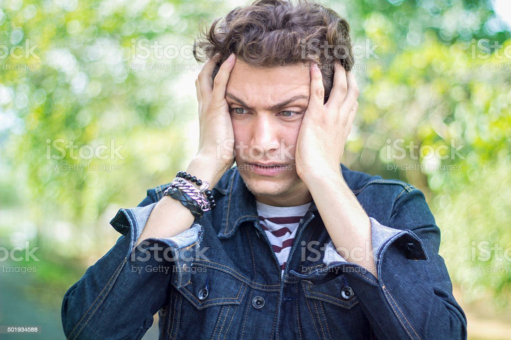 Portrait of frustrated teenage boy against blurred background stock photo