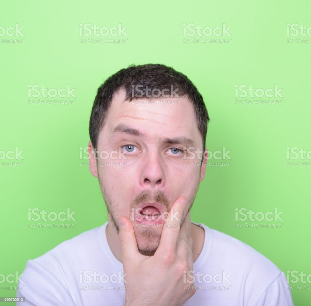 Portrait of funny cluelles man against green background stock photo