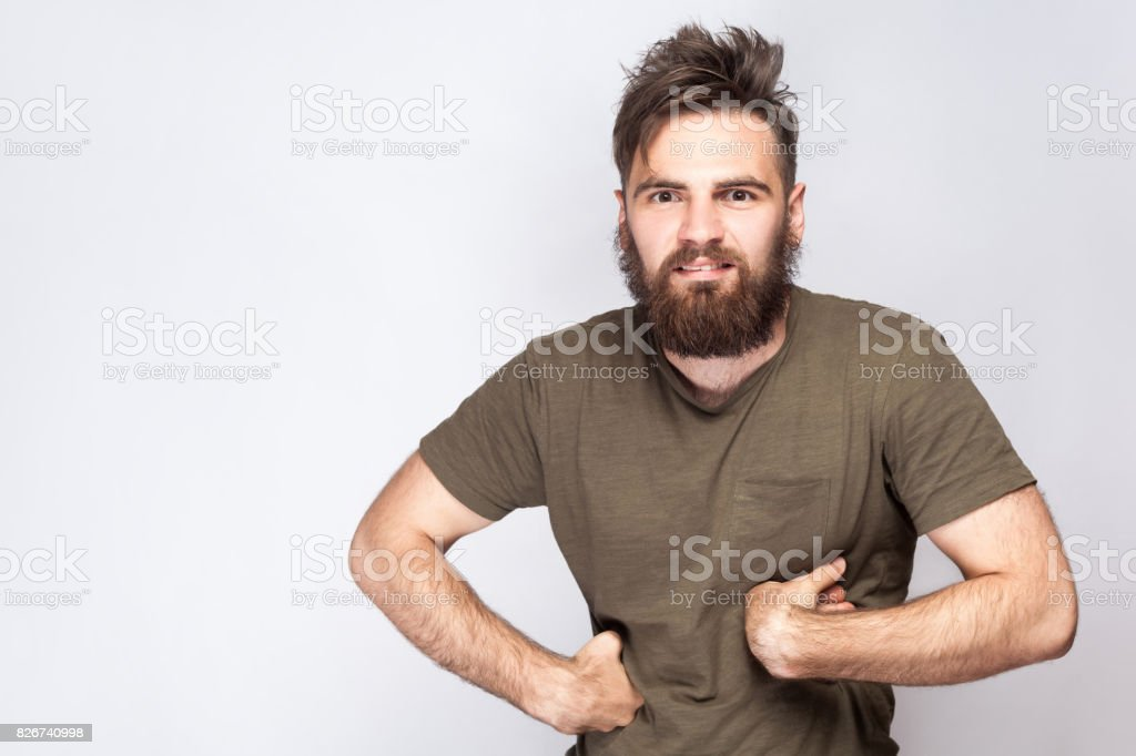 Portrait of funny crazy bearded man with dark green t shirt against light gray background. stock photo