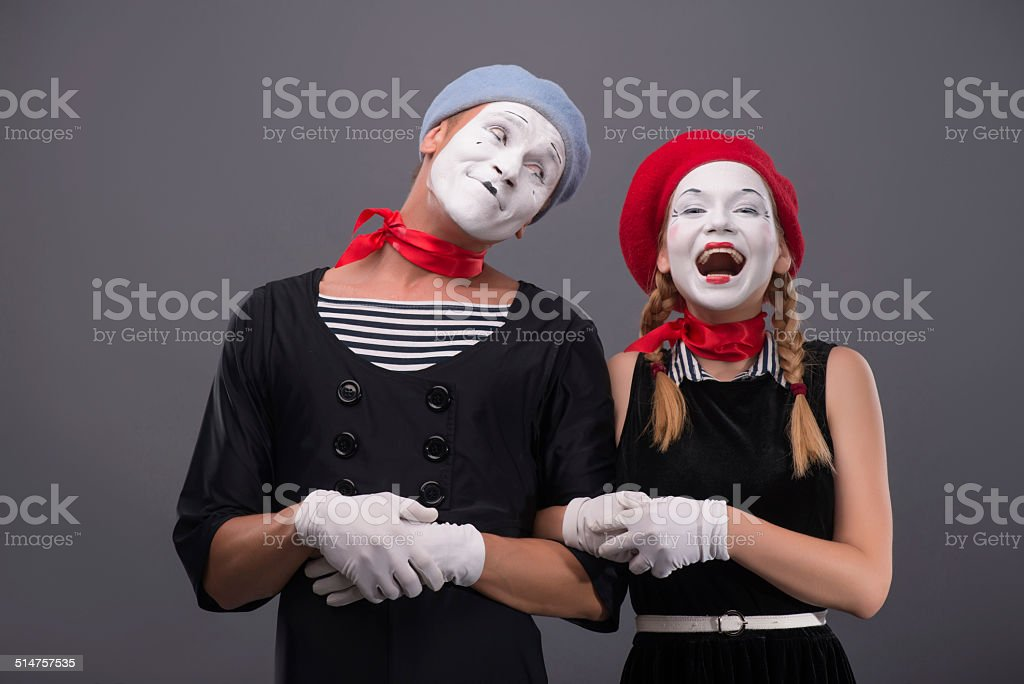 Waist-up portrait of mime couple with white faces, male mime looking...