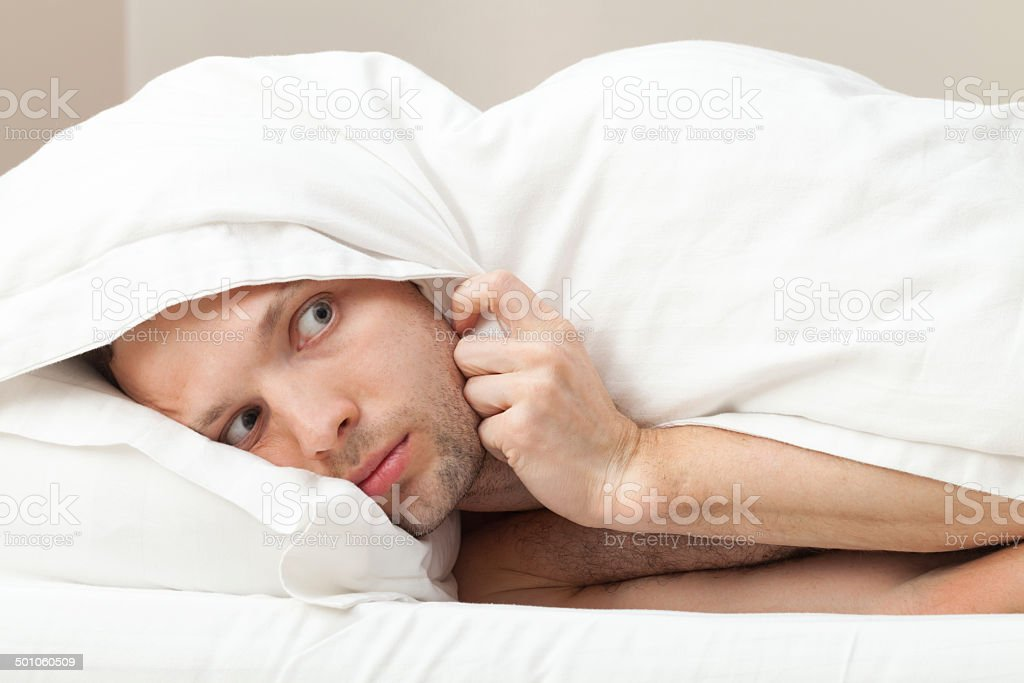 Portrait of funny scared Young Caucasian man in bed stock photo