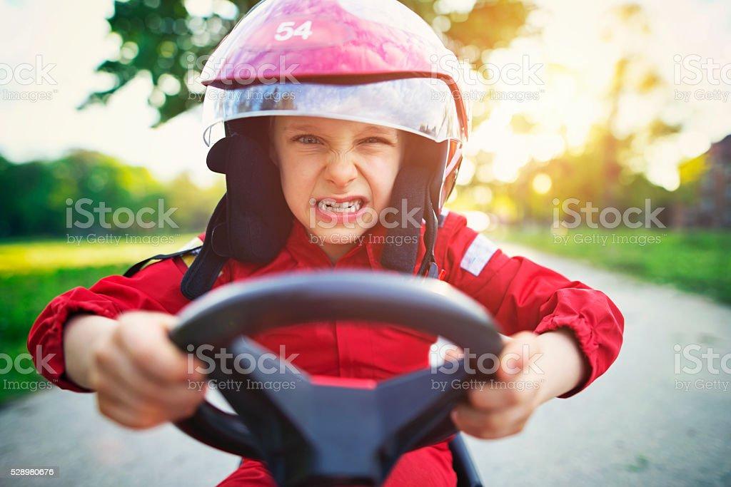 Portrait of furious little boy riding a fast go-kart. stock photo