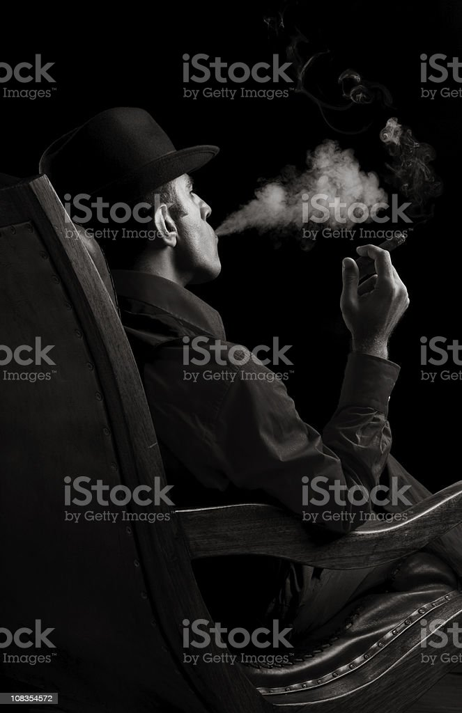 Portrait of gang member sitting on armchair and smoking cigar stock photo