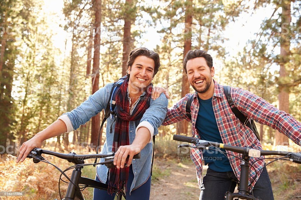 Portrait Of Gay Male Couple Cycling Through Fall Woodland stock photo
