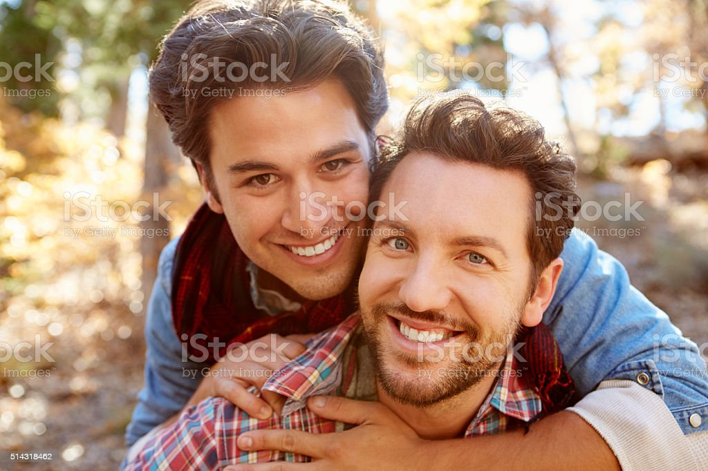 Portrait Of Gay Male Couple Walking Through Fall Woodland stock photo