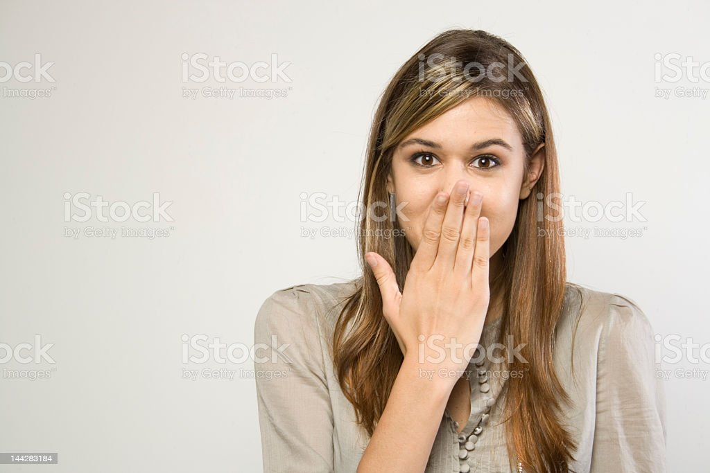 Portrait of giggling girl covering her mouth stock photo