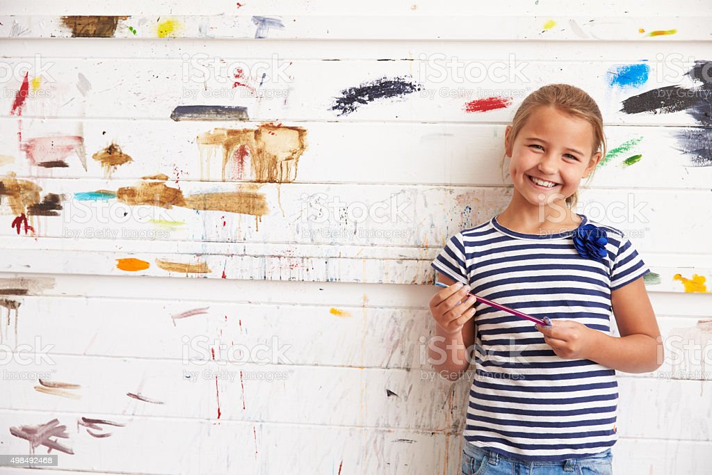 Portrait Of Girl Against Paint Covered Wall In Art Studio stock photo