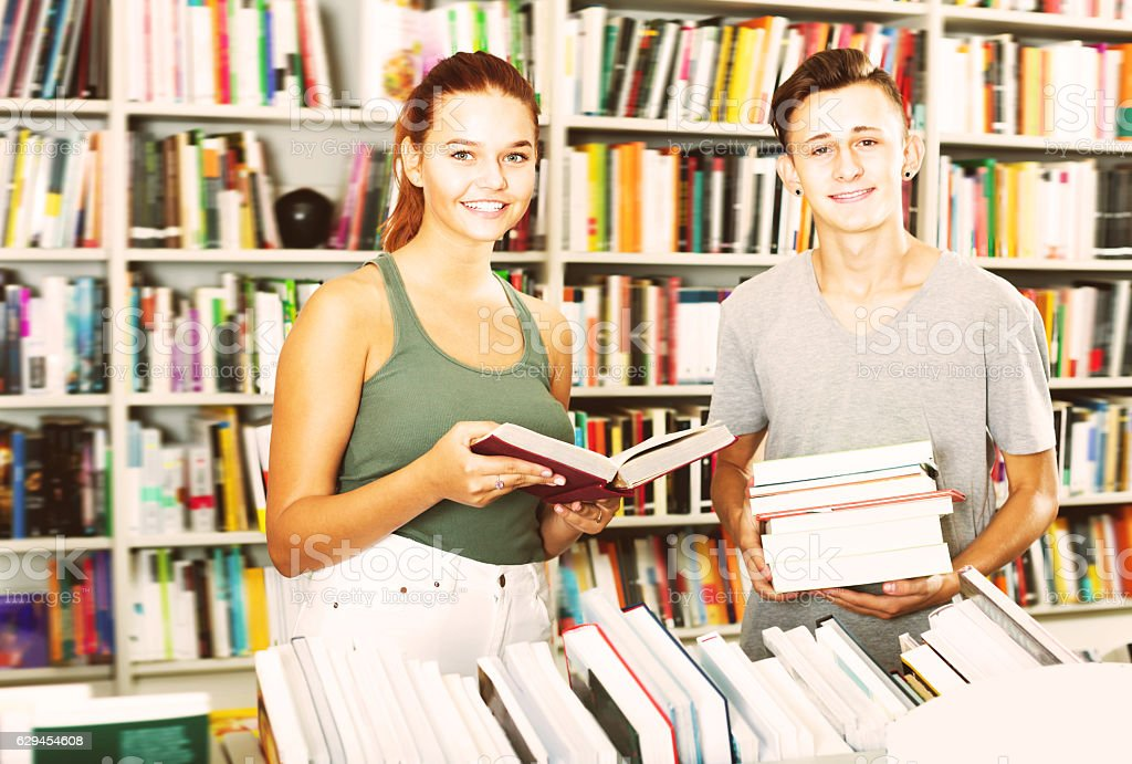 Portrait of girl and boy taking new books stock photo