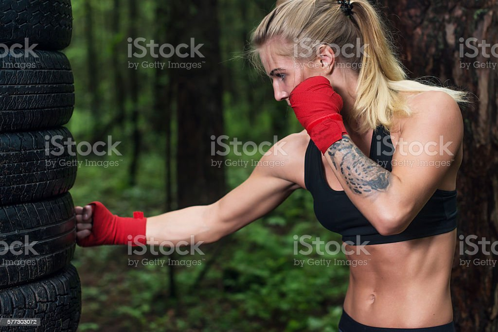 Portrait of girl boxer doing uppercut kick working out outdoors. stock photo